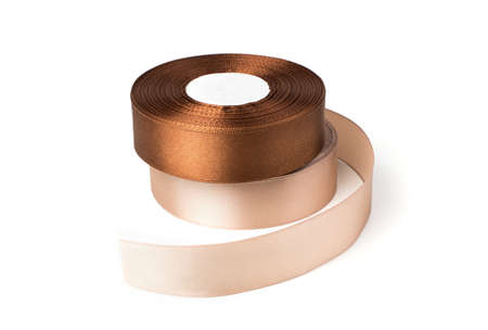Beige and brown satin ribbons isolated on a white background. The concept of sewing accessories.