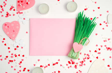 Pink envelope, green bouquet and hearts on a light background. Holiday background with space to copy.