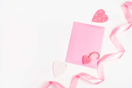 Hearts, ribbon and pink envelope on a light background. Top view with space to copy. The Concept Of Valentines Day.