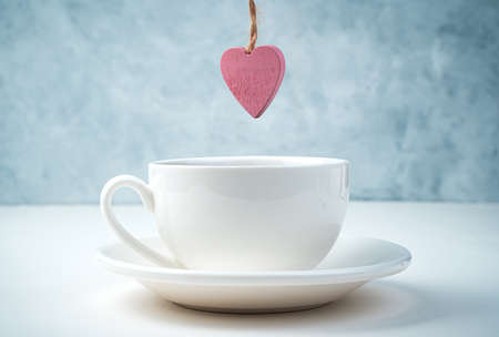 A pink heart hangs over a coffee Cup and saucer on a white and gray background. Side view. Concept February 14.