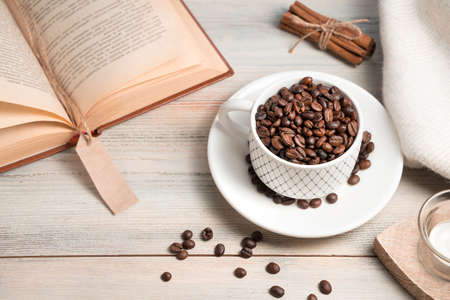 Coffee background with grains poured into a Cup and a book on a light background. Side view.