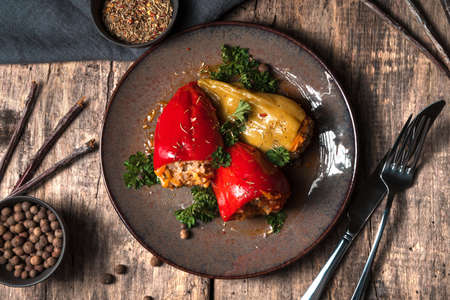 Brown plate with Bulgarian stuffed peppers and herbs on a wooden background. The view from the top. The concept of proper nutrition.