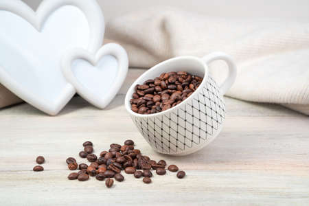 Coffee beans spill out of a tilted Cup on a light background. Side view. Concept of coffee backgrounds.