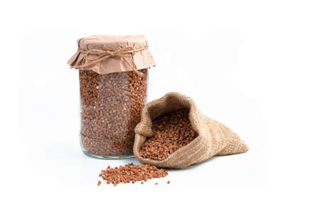 Buckwheat in a jar and in a linen bag on a white background. Side view with space for copying. Grocery background.