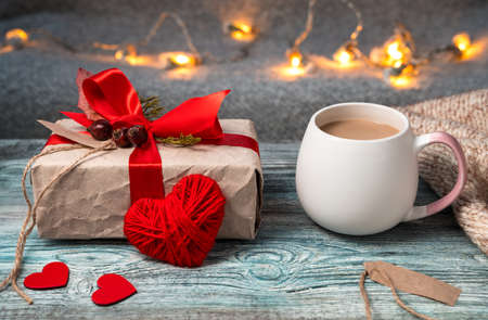 Romantic composition with a Cup of coffee and a gift on a festive cozy background. Side view with space for copying. Concept February 14.