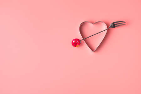 Metal heart pierced with a fork on pink
