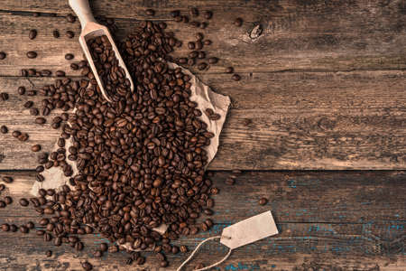 Spilling coffee beans from a linen bag and a wooden spatula on a white background. Side view with space for copying. Coffee background.