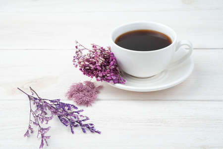 Purple flowers and coffee on a white background. Side view, with space to copy. The concept of International Womens Day. Standard-Bild