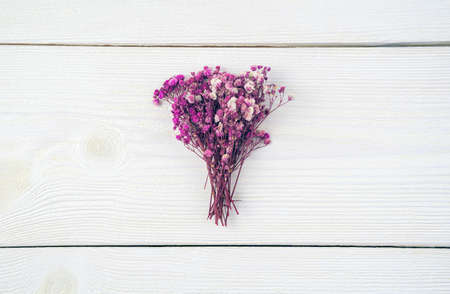 A bouquet of flowers on a light wooden background. Top view with space to copy. Concept of festive backgrounds, International Womens Day.