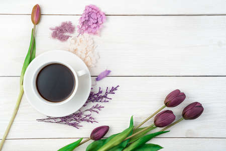 A cup of coffee and flowers on a light background. Top view with space to copy. Concept of festive backgrounds, International Womens Day.