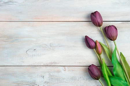 Bouquet with tulips on a light wooden background. Top view with space to copy. Concept of March 8. Standard-Bild