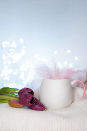 A bouquet of tulips, a mug with feathers, a sweater on a light background with burning lights. Side view, with space to copy. The concept of holiday backgrounds.