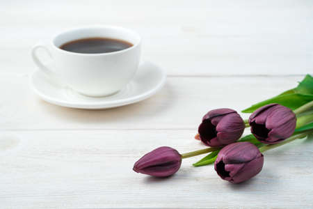 Purple tulips and a white coffee cup in the background on a light wooden background. Side view, with space to copy. Concept of March 8, spring.