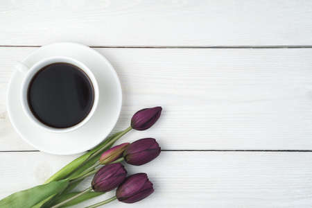 Festive background with a cup of coffee and tulips on a light wooden background. Top view, with space to copy. Standard-Bild