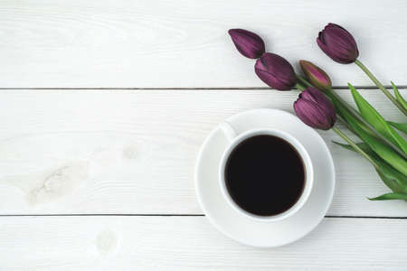 A cup of coffee on a saucer and a bouquet of tulips on a light wooden background. Top view, with space to copy. Concept of festive backgrounds, March 8. Standard-Bild