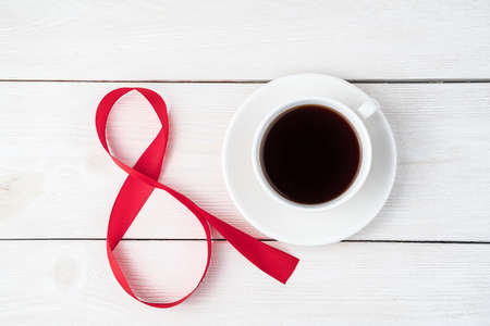 White ceramic coffee cup and the number 8 in red satin ribbon on a white wooden background. Top view, with space to copy. Concept of March 8, spring. Standard-Bild