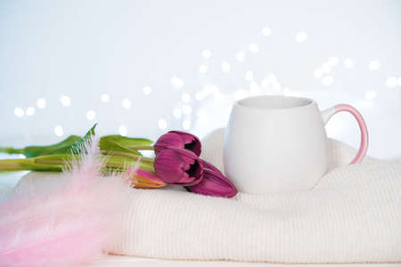 A bouquet of tulips, a mug of coffee, pink feathers and a sweater on a light background with burning lights. Side view, with space to copy. The concept of holiday backgrounds.
