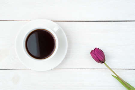 March 8, one tulip and a cup of coffee on a light wooden background. Top view, with space to copy. Concept of festive backgrounds, spring.