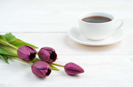Purple flowers and a white coffee cup in the background on a light wooden background. Side view, with space to copy. Concept of March 8, spring.