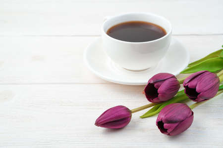 Festive background with tulips and a white coffee cup on a light wooden background. Side view, with space to copy. Concept of March 8, spring.