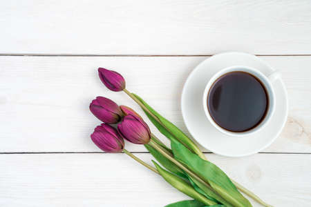 March 8, tulips and coffee in a white cup on a light wooden background. Top view, with space to copy. Concept of festive backgrounds, spring. Standard-Bild