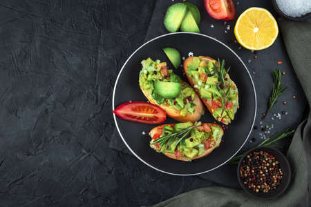 Three toasts with guacamole and rosemary on a black background. Top view, with space to copy. The concept of healthy food.