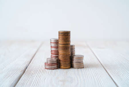 Coins in stacks in the form of towers on a light background. Side view with copy space. The concept of finance, business.