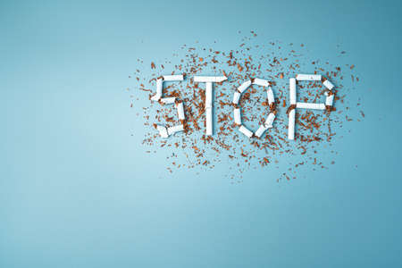 The word stop from broken cigarettes on a blue background. The concept of the dangers of smoking.