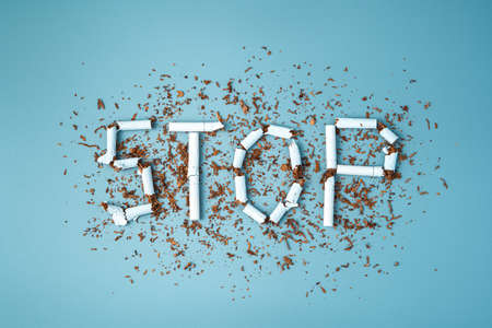 The inscription stop of cigarettes on a blue background. Top view, horizontal. The concept of the dangers of smoking. Фото со стока