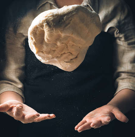 Kneading the dough, the cook throws the dough. Levitation of food. Cooking concept.
