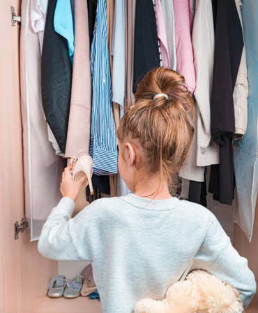 Cute little girl smiles against the background of clothes on hangers in the closet. Side view.