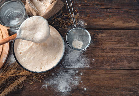 Stirring with a spoon of active starter culture. Ingredients for making bread. Tinted culinary background with copy space. Imagens