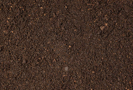 Background with brown dry soil. Pitchfork on top. A concept for your design.