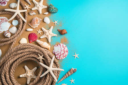 Sand, seashells and rope on a blue background with space to copy. Sea background.