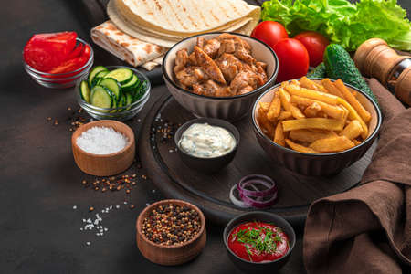 Ingredients for homemade shawarma, burritos, gyros on a brown background. Fried meat, French fries, vegetables and pita bread. Lunch.