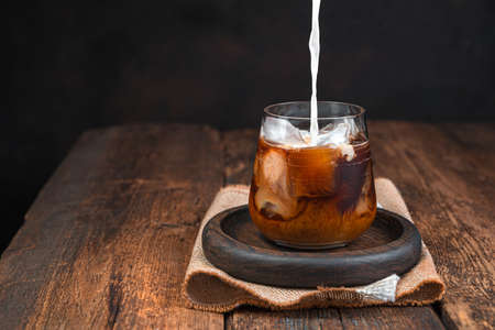 Iced coffee with milk, cold drink in a glass on a dark background. Pouring milk into coffee. Copy space.