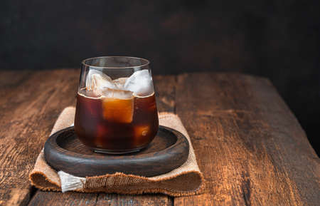 Iced coffee in a clear, steamed glass on a brown background. Side view, copy space.
