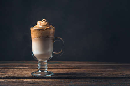 Dalgona coffee in a tall clear glass on a brown tinted background. Side view, copy space. Stockfoto