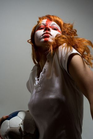 english football makeup girl holding worn soccer ball, looking directly into camera photo