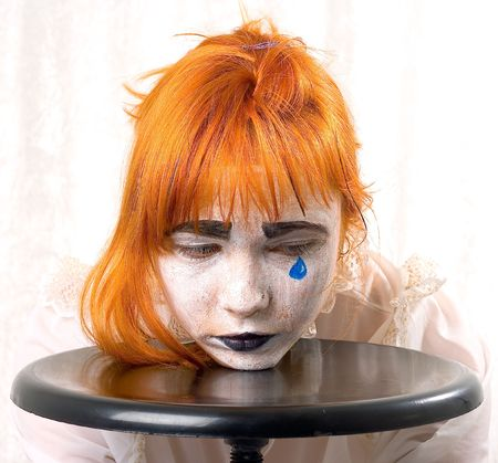 Clown makeup girl with red hair and blue tear photo