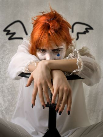sinful: Sad girl in clown makeup with painted wings Stock Photo
