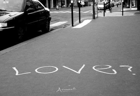 bilingual: black and white grainy film picture of bilingual grafitty on the street of paris, france Stock Photo