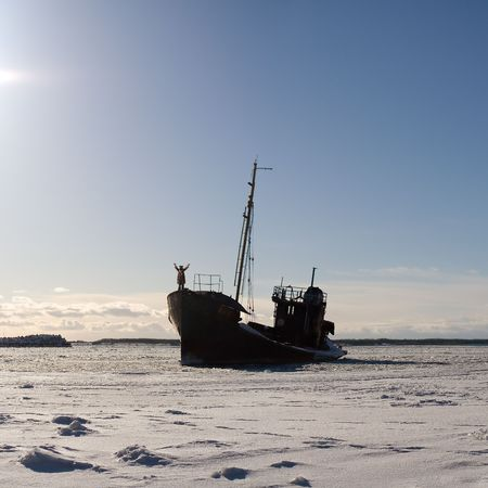 lonely ship in the snowy sea with a man dressed like a bear onboard photo
