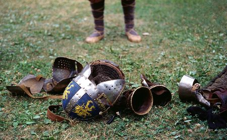 legs in a bast shoes, helmet and armour on the ground after the tournament photo