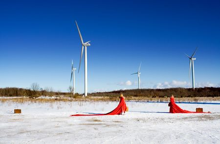 conservational: red ladies on snow field with windmills