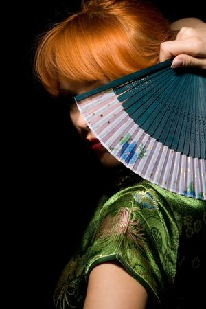 redhead girl in chinese dress playing with fan Stock Photo - 448368