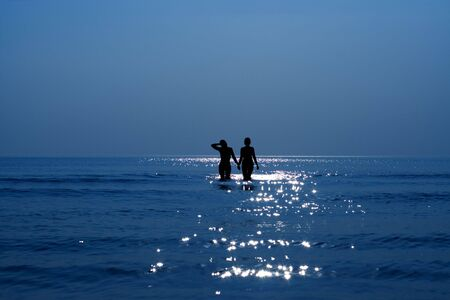 silhouette of two girls holding hands in the sea photo