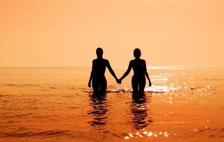 Silhouette Bild von zwei Bikini M�dchen H�ndchen haltend