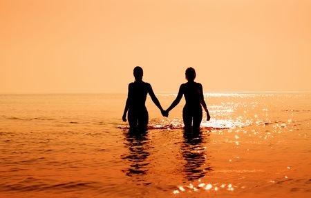 silhouette image of two bikini girls holding hands photo