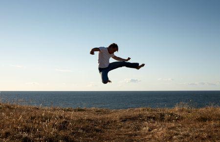 silhouette image of martial arts master jump-kicking photo